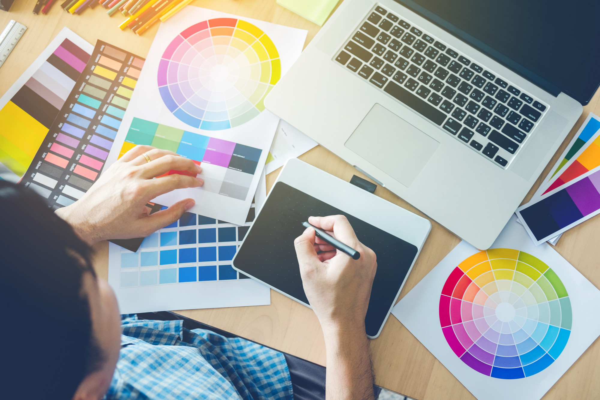 graphic designer with laptop and color wheels